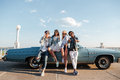 Cheerful young people standing near vintage cabriolet Royalty Free Stock Photo