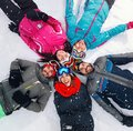 Cheerful skiers lying on snow and having fun