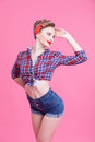 Cheerful young woman is evincing her sexuality portrait of pin up girl standing and posing with joy she raising arm to head the Royalty Free Stock Photo
