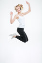 Cheerful young woman listening to music with headphones and jumping attractive in the air over white background Stock Images