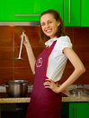 Cheerful young woman preparing food on kitchen Stock Photo