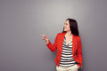Cheerful young woman in red jacket pointing at empty copyspace over grey background Stock Photo