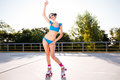 Cheerful young woman riding on roller skates outdoors Royalty Free Stock Photo