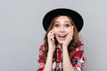 Cheerful young woman standing over grey wall talking by phone. Royalty Free Stock Photo