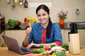 Cheerful young woman using a laptop in her kitchen with grocery bag full of fruits and vegetables Stock Image