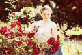 Cheerful young woman working with bush roses with horticultural Royalty Free Stock Photo
