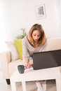 Cheerful young woman working at home with laptop Stock Photo
