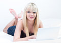 Cheerfull girl lying in bed with laptop Stock Photography