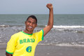 Cheering brazilian guy at beach football fan from brazil standing the with the ocean in the background and laughs camera Stock Photo