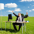 Cheering businessman happy sitting and on greenfield Royalty Free Stock Images