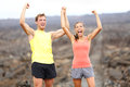 Cheering celebrating happy fitness runner couple with arms raised up in winning gesture expression outdoors on trail running path Royalty Free Stock Images