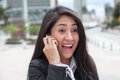 Cheering latin woman talking at phone in the city Royalty Free Stock Photo