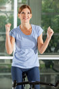 Cheering woman on bike in fitness Royalty Free Stock Photography