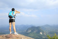 Cheering woman hiker yell at mountain peak cliff Royalty Free Stock Image