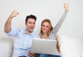 Cheering young couple on a sofa with notebook Royalty Free Stock Photo