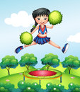 A cheerleader jumping with her green pompoms above a trampoline Royalty Free Stock Photo