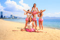 Cheerleaders perform straddle stunt with one split on beach in white pink uniform girl does sand against resort city Royalty Free Stock Photography
