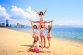 Cheerleaders perform straddle stunt with one split on beach in white pink uniform girl does sand against resort city Royalty Free Stock Photo