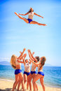 Cheerleaders perform toe touch toss on beach squad of in white blue uniform performs against azure sea wind shakes long hair Stock Photos