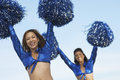 Cheerleaders with pom poms raised portrait of two happy against the sky Stock Photography