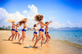 Cheerleaders stand in line hands over head in shallow water Royalty Free Stock Photo