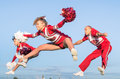 Cheerleaders team with male coach performing a synchronized jump Stock Photography