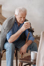 Cheerless aged man holding a cup