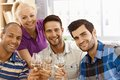 Cheers closeup photo of celebrating friends smiling happy clinking glasses looking at camera Stock Images