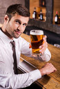 Cheers handsome young man in shirt and tie toasting with beer and looking at camera while sitting at the bar counter Stock Photography