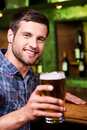 Cheers handsome young man toasting with beer and looking at camera with smile while sitting at the bar counter Stock Photo
