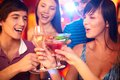 Cheers portrait of joyful friends toasting at birthday party with focus on happy girl and guy Stock Image