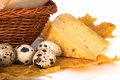Cheese allsorts in a wicker basket on yellow autumn leaves with quail eggs light background shallow depth of field Stock Photos