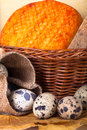 Cheese allsorts in a wicker basket on yellow autumn leaves with quail eggs shallow depth of field Royalty Free Stock Photos