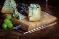 Cheese board stilton mature blue mouldy and grapes green black Stock Photo