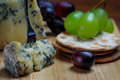 Cheese board stilton mature blue mouldy and grapes green black Royalty Free Stock Photography
