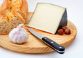 Cheese, bread, hazelnuts and knife on wood plate Stock Image