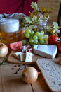 Cheese, bread, onions, wine, tomatoes and beer Royalty Free Stock Photo