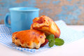 Cheese buns with cherry jam. Blue cup with milk Royalty Free Stock Photo