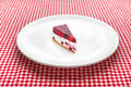 Cheese cake on white plate a kitchen table red and checkered tablecloth in background Royalty Free Stock Images