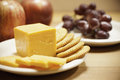 Cheese crackers and fruit closeup yellow cheddar is sliced on a white plate with round another plate of red seedless grapes sits Stock Images