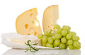 Cheese culinary with wine grapes on white Stock Photography