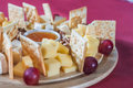 Cheese with grapes and crackers different varieties of nuts honey on wooden plate Royalty Free Stock Photo