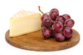 Cheese with grapes on a wooden board isolated white Stock Photography