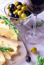 Cheese with green and black olives and glass of red wine Royalty Free Stock Photo