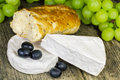 Cheese with olives grapes and bread on old wooden table Stock Image