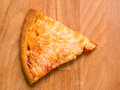 Cheese pizza slice of on wood Royalty Free Stock Images