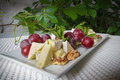Cheese plate with grapes and nuts Royalty Free Stock Photo