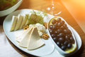 Cheese plate with nuts, herbs and black olives on table. Royalty Free Stock Photo