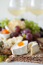 Cheese plate served with grapes, jam, cured melon, crackers and Royalty Free Stock Photo