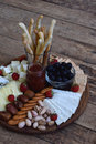 Cheese plates served with grissini, crackers, dates, jam, olives and nuts on wooden background Royalty Free Stock Photo